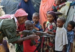 A government soldier on patrol in the streets of Somalia's war-torn capital demonstrates to Somali children how to use a Kalashnikov rifle during a gesture by the soldiers to win the goodwill of the residents of Mogadishu, on September 13, 2009. British intelligence chiefs have warned Prime Minster Gordon Brown's government that the number of young Britons travelling to Somalia to partcipate in terror-training camps is rising noting that the number of people with no direct family connection in Somalia travelling there per year had quadrupled to 100 since 2004. The Shebab, an Al-Qaeda inspired movement, is spearheading a three-month-old offensive to topple Somalia's President Sharif Sheikh Ahmed and has imposed strict Sharia law in areas under its control. AFP PHOTO/ MOHAMED DAHIR