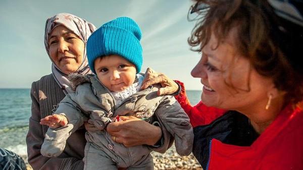 Rfugiati donna e bambino aiutati da volontaria