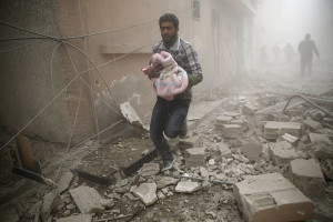 A Syrian man carries a baby wrapped in a blanket following air strikes on the town of Douma in the eastern Ghouta region, a rebel stronghold east of the capital Damascus, on December 13, 2015. At least 28 civilians were killed in heavy bombardment of the besieged Syrian rebel stronghold, including near a school, according to the Syrian Observatory for Human Rights. AFP PHOTO / SAMEER AL-DOUMY