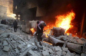 ATTENTION EDITORS - VISUAL COVERAGE OF SCENES OF DEATH AND INJURYA man carries an injured child amidst rubble near a burning vehicle in a site damaged from what activists said was shelling by forces loyal to Syria's President Bashar al-Assad in the town of Douma, eastern Ghouta in Damascus, Syria December 30, 2015. REUTERS/Bassam Khabieh - RTX20JO0